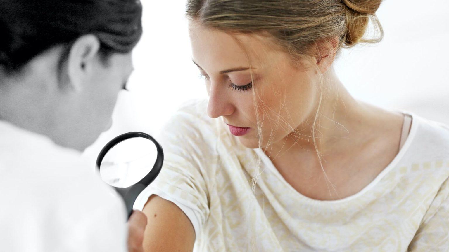 Eine Ärztin untersucht einen Leberfleck auf dem Oberarm einer Frau