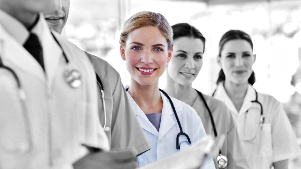 Lächelnde Ärztin in einer Gruppe von Kollegen