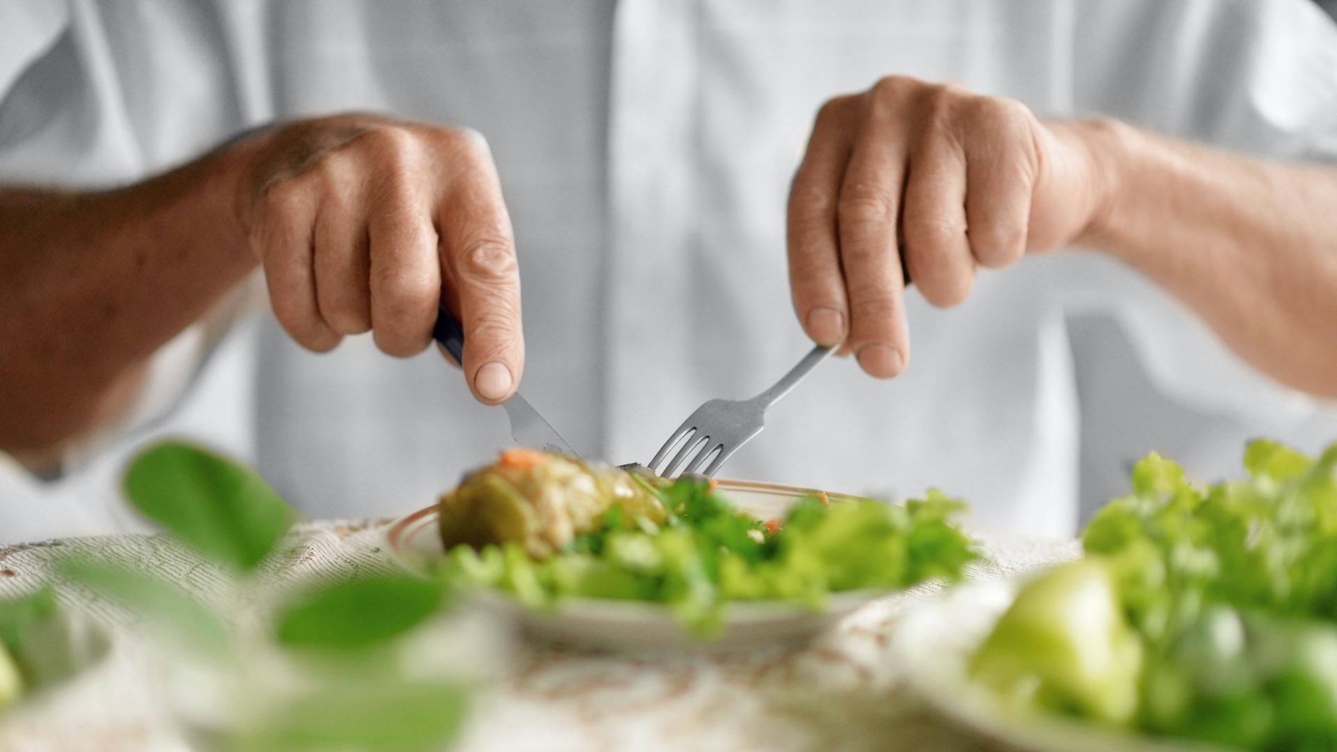 Ältere Person nimmt eine warme Mahlzeit zu sich