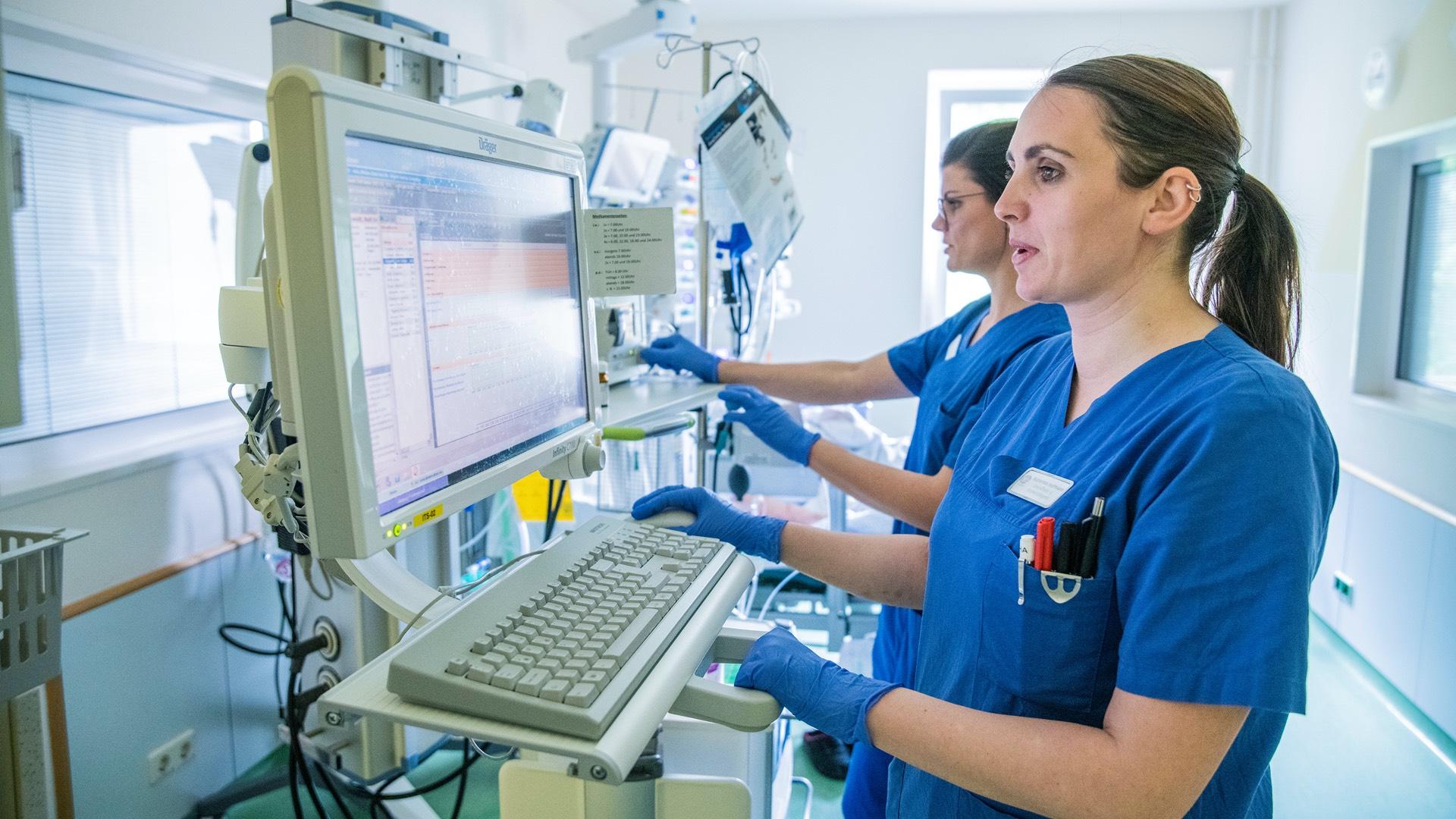 Zwei Intensivpfleger der Lungenklinik Neustadt kontrollieren die Vitalwerte der Patienten