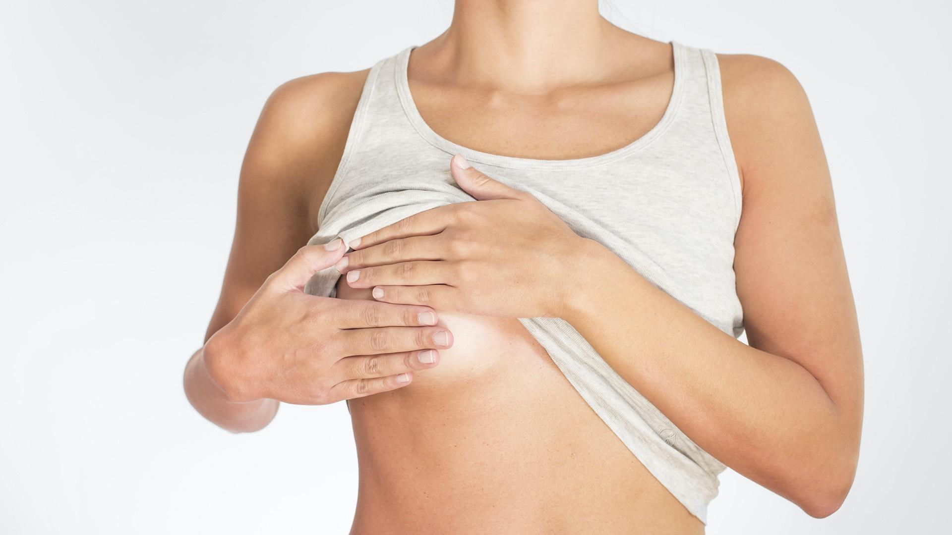 Frau tastet ihre Brust zur Brustkrebsvorsorge ab