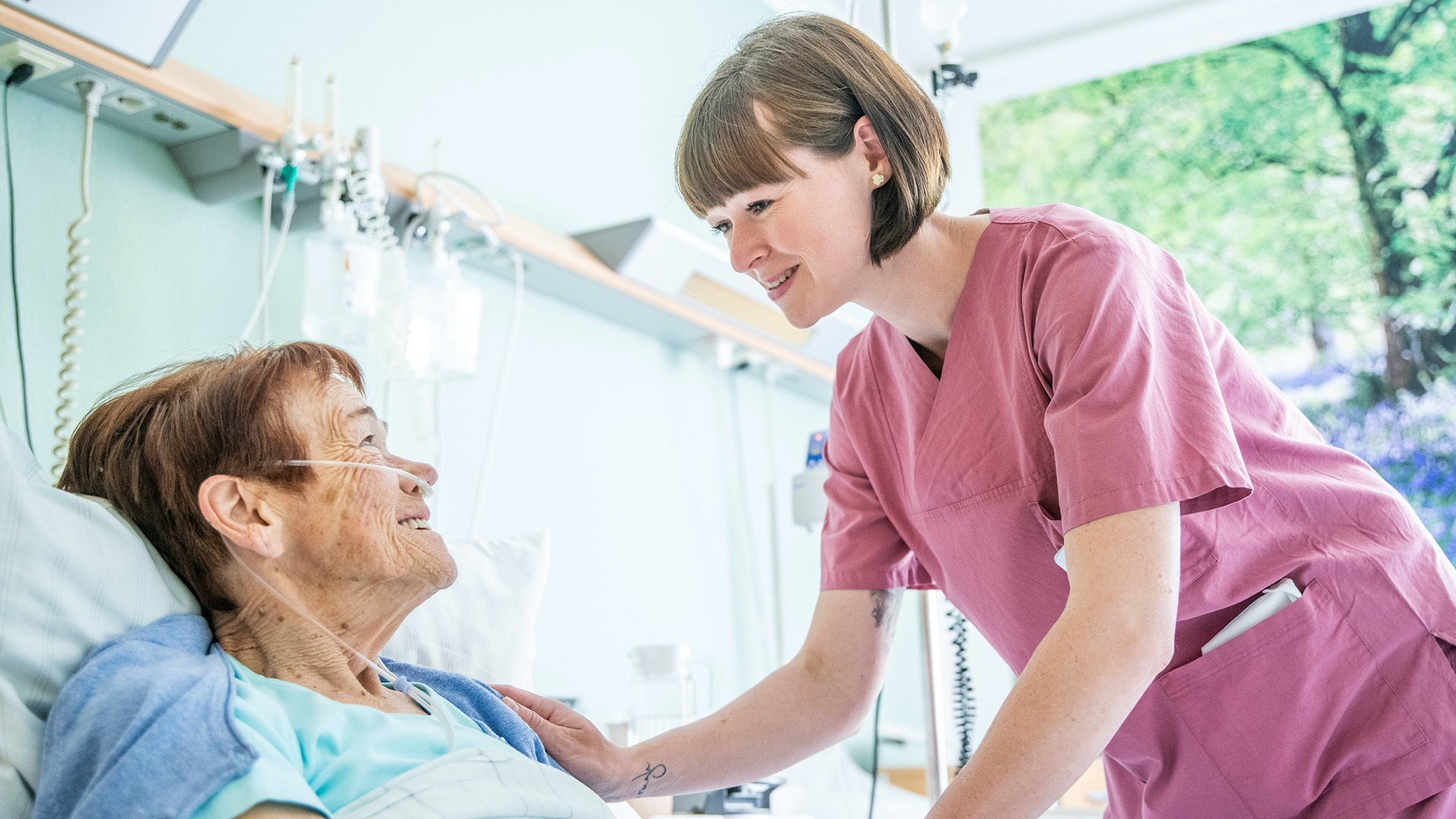 Pflegerin spricht mit Patientin in der Beatmungstherapie
